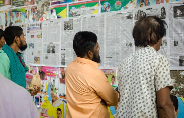 People reading newspapers on a wall in Bangladesh