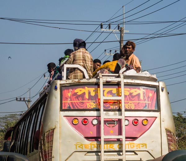 People riding on the roof of a bus in Bangladesh
